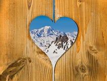 A montanha de Mont Blanc coberta com a neve vista através de um coração de madeira Foto de Stock