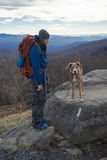 Montanha do homem e do cão que caminha com trouxa imagens de stock