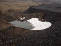 Montanha e lago pretos do carvão vegetal sob a neve fotos de stock royalty free