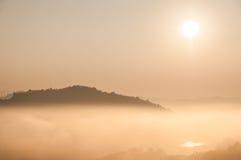 Montanha e névoa no nascer do sol Fotos de Stock