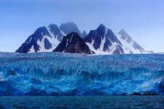 Montanha escura do inverno com neve, gelo azul da geleira com o mar no primeiro plano, Svalbard, Noruega, Europa fotografia de stock royalty free