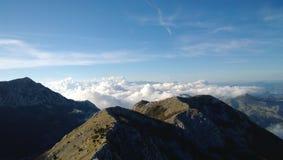 A montanha Lovcen em Montenegro Montanhas tampadas e nuvens brancas macias abaixo dos picos fotos de stock