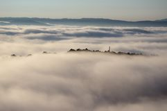 A montanha máxima, montanhas da tampa da névoa densa com fundo é céu azul, ar fresco e névoa no alvorecer foto de stock