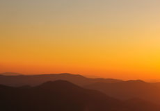 A montanha mínima dá forma no horizonte durante o por do sol Imagem de Stock Royalty Free