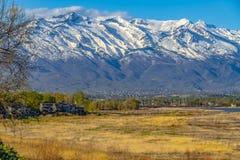 Montanha nevado relevante que eleva-se sobre o vale sob o céu azul em um dia ensolarado foto de stock