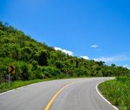 A montanha, o céu, nuvens e a curva da estrada Fotos de Stock Royalty Free
