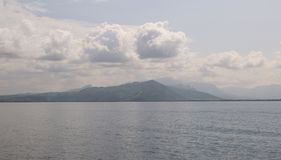 Montanha pelo oceano sob nuvens fotografia de stock
