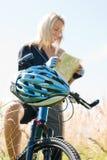 Montanha que biking a busca da mulher nova no mapa Fotos de Stock Royalty Free