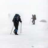 Montanha que caminha o grupo na tempestade da neve fotos de stock