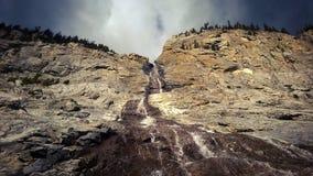 A montanha que rola sobre a água da montanha da luz solar e da cascata das nuvens cai Foto de Stock Royalty Free