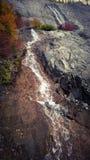 A montanha que rola sobre a água da montanha da luz solar e da cascata das nuvens cai Fotografia de Stock Royalty Free