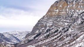 Montanha relevante do panorama com um enrolamento pavimentado da estrada através de sua inclinação nevado foto de stock