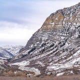 Montanha relevante do quadrado do quadro com um enrolamento pavimentado da estrada através de sua inclinação nevado imagens de stock