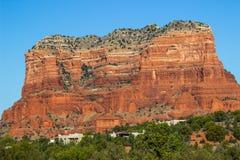 Montanha vermelha da rocha com as camadas que negligenciam casas no Arizona Dese Foto de Stock