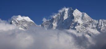 Montanhas altas Kangtega e Thamserku que alcançam fora das nuvens fotografia de stock