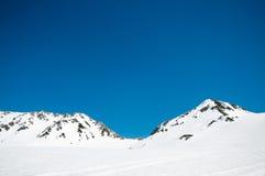 Montanhas altas sob a neve com o céu azul claro Foto de Stock
