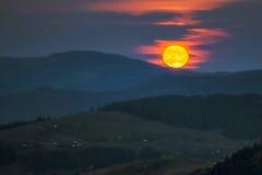 Montanhas Carpathian Uma Lua cheia de aumentação sobre as montanhas de Imagens de Stock Royalty Free