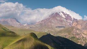 Montanhas caucasianos Pico a igreja e de montanha velhas de Kazbek com neve tampam raios do sol com as sombras moventes vídeos de arquivo