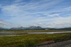 Montanhas distantes sobre pântanos imóveis da água imagens de stock