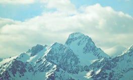 Montanhas do inverno com o filtro do vintage do moderno das nuvens foto de stock