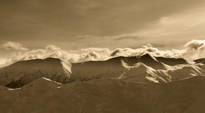 Montanhas do inverno do Sepia em nuvens da noite e da luz solar Fotografia de Stock Royalty Free