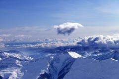 Montanhas do inverno em nuvens agradáveis da noite e da luz solar Fotos de Stock Royalty Free