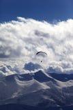 Montanhas do inverno na noite e na silhueta do paraglider Imagem de Stock Royalty Free