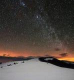 Montanhas do inverno sob o céu nebuloso estrelado Imagens de Stock