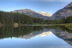 Montanhas e árvores que refletem em um lago - Banff, Canadá Foto de Stock Royalty Free