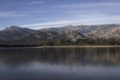 Montanhas e árvores refletidas sobre a água de um lago foto de stock