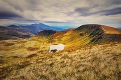 Montanhas e campo da paisagem sob o céu azul Imagens de Stock Royalty Free