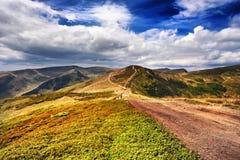 Montanhas e campo da paisagem sob o céu azul Fotos de Stock