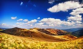 Montanhas e campo da paisagem sob o céu azul Imagem de Stock