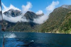 Montanhas e nuvens em Milford Sound a bordo um navio de cruzeiros fotos de stock royalty free