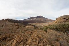 Montanhas em torno do vulcão Teide, coberto em parte pelas nuvens C?u azul brilhante Parque nacional de Teide, Tenerife, Ilhas Ca imagens de stock