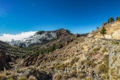 Montanhas em torno do vulcão Teide, coberto em parte pelas nuvens C?u azul brilhante Parque nacional de Teide, Tenerife, Ilhas Ca foto de stock royalty free