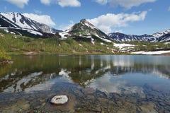 Montanhas, lago da montanha e nuvens no céu azul Fotos de Stock