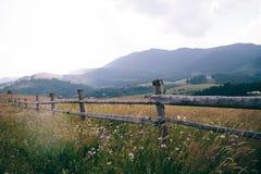 Montanhas na névoa A vista na distância cerca de madeira e abundância do espaço Fotografia de Stock Royalty Free