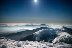 Montanhas na neve no céu noturno Imagens de Stock
