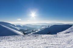 Montanhas nevado do inverno no dia agradável em Carpathians, Dragobrat do sol, Ucrânia Fotografia de Stock Royalty Free
