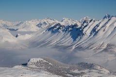 Montanhas nevado e vale Coverd na névoa fotos de stock royalty free