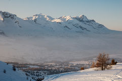 Montanhas nevado e vale Coverd na névoa foto de stock