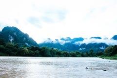 Montanhas nevoentas cercadas pelo rio e pela floresta Foto de Stock
