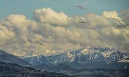 Montanhas, nuvens e avião enormes do voo Foto de Stock Royalty Free