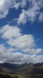 Montanhas pequenas sob o céu e nuvens grandes Fotos de Stock