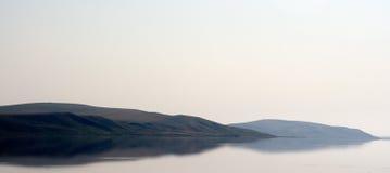Montanhas refletidas no mar fotografia de stock