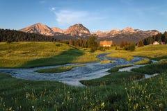 Montanhas, rio, e prado Fotografia de Stock