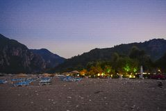 Montanhas Sunbeds do mar das palmas da praia no crepúsculo imagens de stock