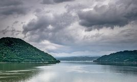 Montanhas, um grande rio e um céu com muitas nuvens pretas fotos de stock royalty free