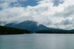 Montanhas verdes e nebulosas com lago Imagens de Stock Royalty Free